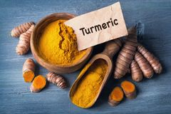 Turmeric powder and roots. Turmeric powder and fresh roots royalty free stock photography