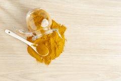 Turmeric powder in glass bowl. On wood- curcuma longa organic wooden natural yellow medicine herbal background root healthy closeup food indian ingredient stock images