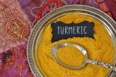 Turmeric powder. Turmeric over indian patchwork carpet Royalty Free Stock Images