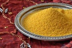 Turmeric powder. Turmeric over indian patchwork carpet Royalty Free Stock Photo
