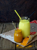 Turmeric powder, paste and latte on wooden background. Ayurvedic healthy golden drink with coconut milk and ghee for beauty and he Stock Image
