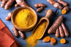 Turmeric powder and roots. Turmeric powder and fresh roots Royalty Free Stock Photo