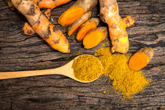 Turmeric powder in spoon and roots on wooden plate Stock Image