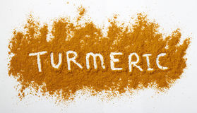 Turmeric powder. Sprinkled on a natural colored background. The word turmeric has been spelled out across the powdered surface Royalty Free Stock Photos