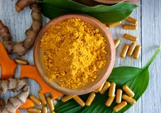 Turmeric powder and turmeric capsules on wooden background. Turmeric powder and turmeric capsules on wooden royalty free stock photo
