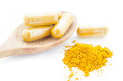 Turmeric powder and a wooden spoon with herbal capsule. Royalty Free Stock Photo