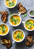 Turmeric pumpkin vegetarian soup on grey background, top view. Flat lay butternut squash soup served in mugs Stock Image