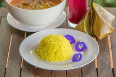 Turmeric Rice and Butterfly pea on white plate. Tradition Thai food on a wooden table. Thai style. Shallow dept of field. Close. royalty free stock photo