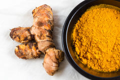 Turmeric root with bowl of powder on white cloth background. Piece of turmeric root or Curcuma longa by bowl of turmeric powder on white cloth background, macro Royalty Free Stock Photography