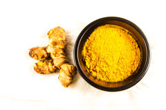 Turmeric root with bowl of powder on white cloth background. Piece of turmeric root or Curcuma longa by bowl of turmeric powder on white cloth background, macro Royalty Free Stock Images