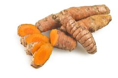 Turmeric root and some slices. On a white background Stock Photos