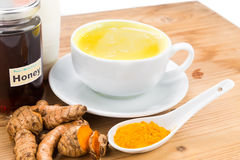 Turmeric roots with milk and honey drinks for beauty and health. Stock Photography
