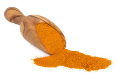 Turmeric Spice. In an olive wood scoop over white background Stock Photo