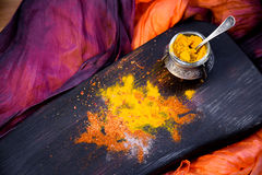 Turmeric with spices on a wooden Board. Turmeric with spices in a pepper pot on textured wooden Board in Oriental style Stock Photo