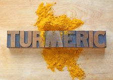 Turmeric word in wood type. The word turmeric in antique old wood type on a cutting board with the spice sprinkled over Stock Images