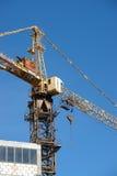 Turmkran auf Baustelle gegen blauen Himmel Stockbilder