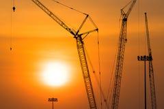Turmkran auf einer Baustelle bei Sonnenuntergang stockbilder