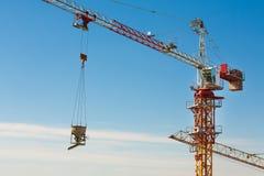 Turmkran, der herauf einen Zementeimer am Baubereich anhebt Lizenzfreie Stockfotografie