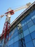 Turmkran, der zu einem modernen Gebäude arbeitet Lizenzfreie Stockfotografie