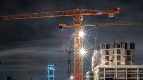 Turmkrane an einer Baustelle in der Nachtstadt lizenzfreie stockfotos