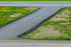 The turn of the airport landing runway road with painted white yellow horizontal signals and lights Stock Photos