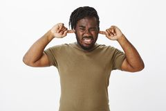 Turn annoying sound off. Portrait of displeased uncomfortable plump guy with dark skin, closing ears with index fingers. Frowning and grimacing from dislike stock image