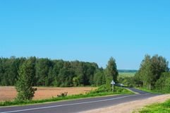 Turn of asphalt road crossing a rural field Royalty Free Stock Photography