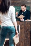 Turn back brunette girl holding book in her hand. Strict teacher looking at his female student while standing at rostrum.  stock photos