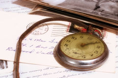 Turn back time. Old pocket watch lying on some old letters and photos. Stamp cancelation is from 1968 Stock Photos
