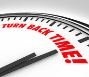 Turn Back Time Clock Reverse Aging Flashback. Turn Back Time words on a clock face to illustrate the reversing of aging, flashback or looking to the past or Royalty Free Stock Photo