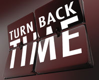 Turn Back Time Retro Clock Flipping Tiles Reverse to Past. The words Turn Back Time on flipping tiles on a retro clock to illustrate going backward to the past Stock Photography