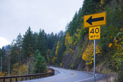 Turn of beautiful autumn road with traffic sign arrows Stock Photography
