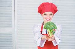 Turn broccoli into favorite ingredient. How to cook broccoli. Raw food diet. Broccoli nutrition value. Woman. Professional chef hold raw broccoli vegetable stock photo