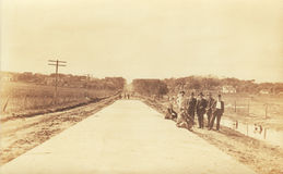 Turn of the Century Road Builders. Photo taken around 1900 in Nebraska showing a group of men standing next to a newly paved road Royalty Free Stock Photography