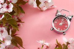 Turn clocks on hour ahead, star of daylight savings time and reminder to spring forward concept with alarm clock on pink. Background with springtime flowers and royalty free stock photography
