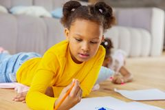 Attentive brunette girl staring at yellow pencil. Turn on imagination. Beautiful kid expressing positivity while creating picture royalty free stock images