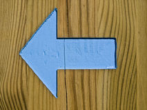 Turn Left. Sign of an arrow painted in blue on a wooden plank, pointing to the left of the image Stock Photos