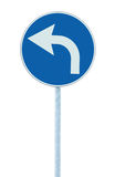 Turn left ahead sign, blue round isolated roadside traffic signage, white arrow icon and frame roadsign, grey pole post, large. Detailed closeup Stock Photo