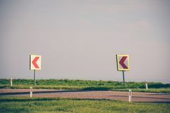 Turn left sign on a country road. Road signs warning drivers about ahead dangerous curve royalty free stock photo