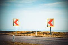 Turn left sign on a country road. Road signs warning drivers about ahead dangerous curve royalty free stock photography