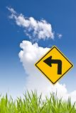 Turn left sign with grass and nice sky Stock Photos