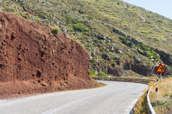 Turn left warning sign. On a curve empty road. Brown cliff on the left side of road royalty free stock photo