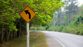 Turn left warning sign. On a curve road royalty free stock image