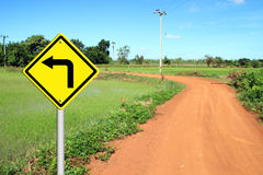 Turn left warning sign with soil road. In countryside Stock Images