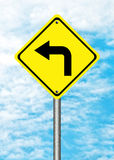 Turn left yellow traffic sign. On blue sky Stock Photos
