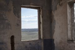 Abandoned house window landscape. A window inside the ruins of an old abandoned house, looking on the countryside Stock Photos