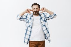 Turn loud music off, it is annoying. Displeased unhappy mature european male in casual clothes, covering ears with index. Fingers, frowning and gazing with royalty free stock photos