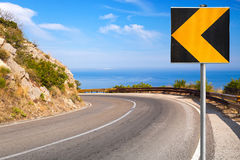 Turn of mountain highway with blue sky. Turn of mountain highway with road sign an and the sea on a background Royalty Free Stock Photo