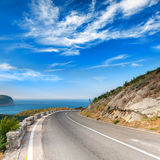 Turn of mountain highway with dramatic sky Royalty Free Stock Images