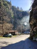 Turn mountain road, because of the rocks beautiful view of the house, the car, smoke from pipe home. beautiful landscape. Turn mountain road rocks beautiful view royalty free stock photography